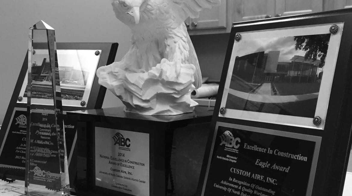 An arrangement of four awards awards that Custom Aire received from Associated Builders and Contractors on a table