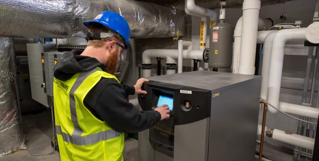 A male Custom Aire HVAC service technician inspects a LAARS commercial boiler in the mechanical room of an apartment building