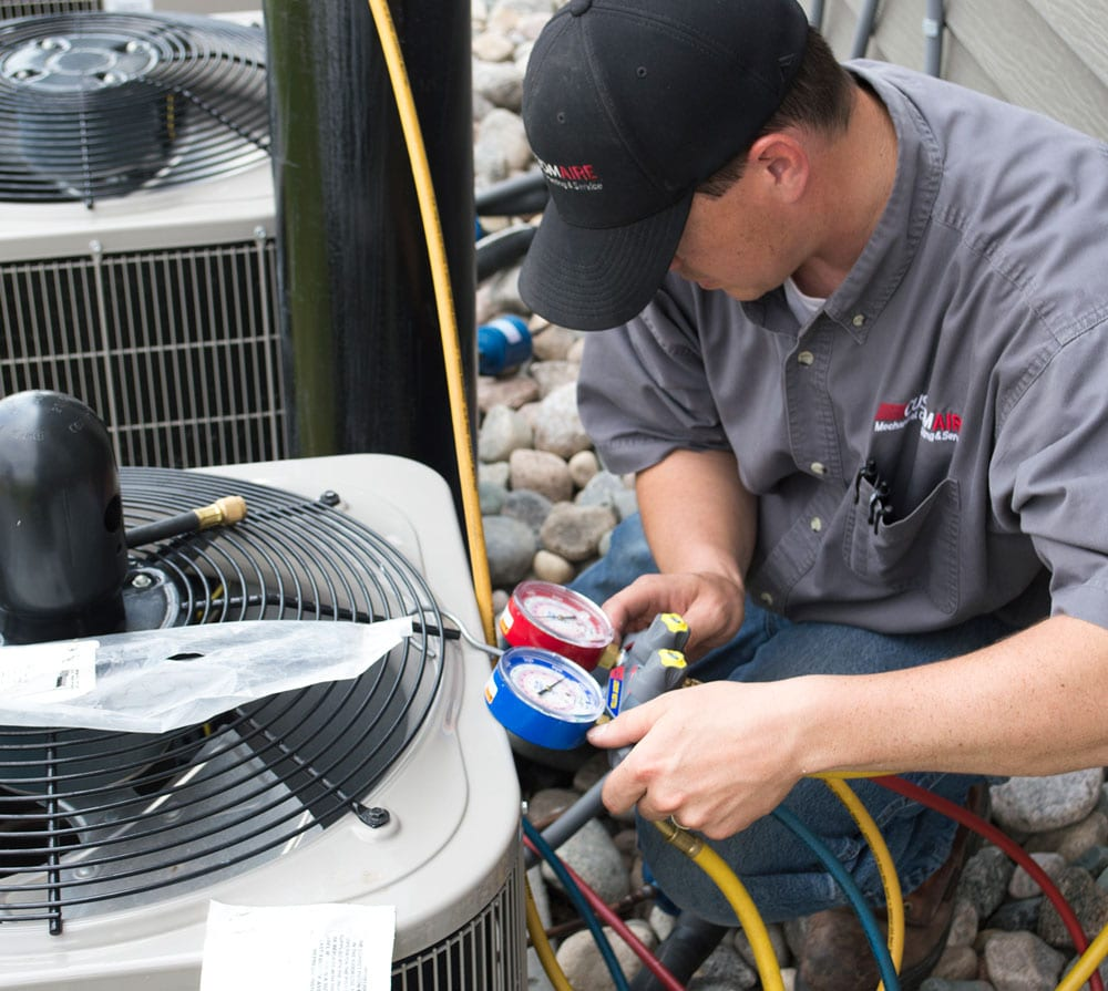 A male Custom Aire HVAC service technician checks the pressure on a set of commercial air conditioners outside an apartment complex